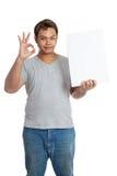 亚洲人展示ok标志举行一个垂直的空白的标志 免版税图库摄影