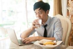 年轻亚洲人工作,当吃与他的膝上型计算机在餐馆时 库存图片