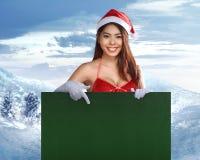 亚洲人拿着一个绿色广告牌的相当圣诞老人妇女 库存照片