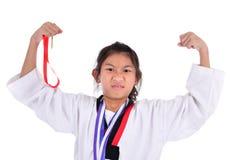 亚洲人显示她的金牌有背景的跆拳道女孩 免版税库存图片