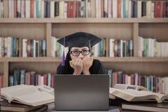 亚洲人毕业生害怕在图书馆的检查 免版税库存照片