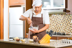 亚洲人烘烤蛋糕在家庭厨房里 免版税库存照片