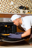 亚洲人烘烤蛋糕在家庭厨房里 免版税库存图片