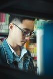亚洲人读书在图书馆里 图库摄影