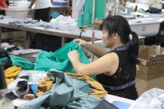 亚洲人给工厂穿衣 库存照片