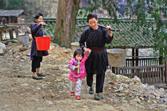 亚洲人去从桶的取指令水在轭和孩子。 免版税图库摄影