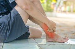 亚洲人医疗保健 他在痛苦中握她的脚腕 库存照片