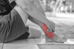 亚洲人医疗保健 他在痛苦中握她的脚腕 库存图片