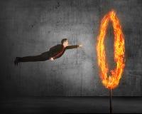 亚洲企业人飞行通过火光环 免版税库存图片