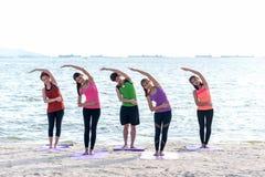 亚洲使战士的人小组摆在海滩、健身、体育、瑜伽和健康生活方式 免版税库存图片