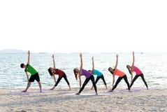 亚洲使战士的人小组摆在海滩、健身、体育、瑜伽和健康生活方式 图库摄影