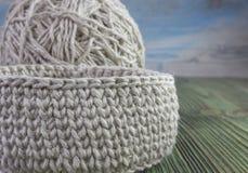 亚麻制土气钩针编织箱子、毛线球和钩针 自然钩针编织纺织品讲解样式 厚实的丝带棉纱品 库存图片