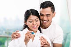 亚洲加上妊娠试验在床上 免版税库存图片