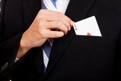 亚洲从口袋的商人拉扯纸牌 免版税库存图片