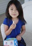 亚洲吃女孩玉米花 免版税库存照片
