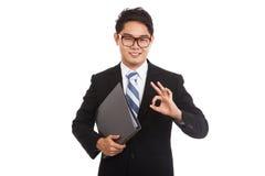 亚洲商人举行文件夹展示OK标志 免版税图库摄影