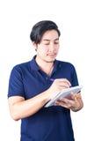 亚洲商人候宰栏和文字笔记本,被隔绝  免版税库存照片