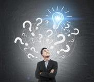 亚洲商人和问号和电灯泡剪影 库存图片