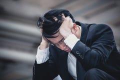 亚洲商人哀伤的忧虑疲倦了和头疼,在workpl的重音 库存照片
