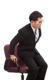 亚洲商人坐充满背部疼痛的办公室椅子 免版税库存照片