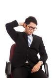 亚洲商人坐充满脖子痛的办公室椅子 库存图片