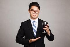 亚洲商人展示每杯红葡萄酒 免版税库存照片