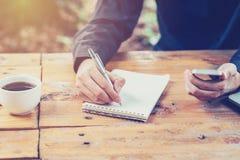 亚洲商人手文字笔记本纸和使用电话  免版税图库摄影