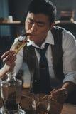 亚洲商人抽烟的雪茄和灼烧的美元钞票 免版税库存图片