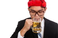 亚洲商人用红色圣诞节帽子饮料啤酒 免版税图库摄影