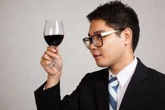 亚洲商人看看红葡萄酒 免版税库存照片