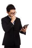 亚洲商人认为与片剂个人计算机 免版税图库摄影