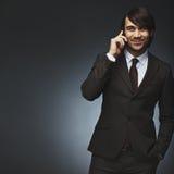 亚洲商人谈话在手机 免版税库存图片