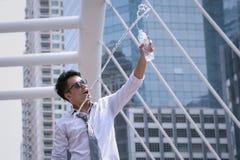 亚洲商人身分和愉快喝水和拿着马胃蝇蛆 免版税库存图片