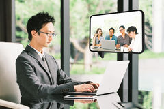 年轻亚洲商人, CEO企业家VDO与不同的商务伙伴小组的电话会议或雇员 免版税图库摄影