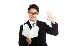 亚洲商人读了一个书展示OK标志 库存照片