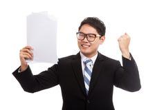 亚洲商人满意对与报告纸的成功 免版税库存图片