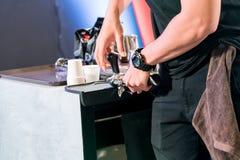 亚洲在逆酒吧的barista砸紧的碾碎的咖啡 库存照片