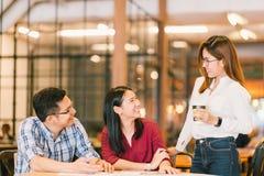年轻亚洲大学生或工友社会会议在咖啡店 库存照片