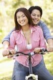 亚洲夫妇两个坐一辆自行车在公园 库存照片