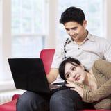 亚洲夫妇冲浪的互联网在家 免版税库存图片