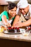 亚洲夫妇可可浆蛋糕在厨房里 免版税库存图片