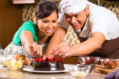 亚洲夫妇可可浆蛋糕在厨房里 免版税库存照片