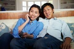 亚洲夫妇坐一起看电视的沙发 免版税库存图片
