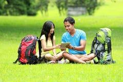 年轻亚洲夫妇坐看片剂个人计算机的公园 库存照片