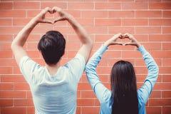 年轻亚洲夫妇愉快爱上姿态递心脏形状 免版税库存照片