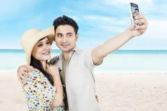 亚洲夫妇拍照片在海滩 免版税库存图片