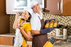 亚洲夫妇烘烤松饼在家庭厨房里 免版税库存照片