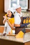 亚洲夫妇烘烤松饼在家庭厨房里 免版税图库摄影