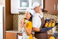 亚洲夫妇烘烤松饼在家庭厨房里 库存图片