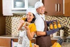 亚洲夫妇烘烤松饼在家庭厨房里 免版税库存图片